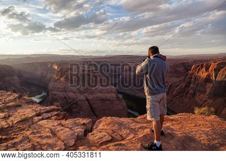 Horseshoe Bend, Arizona / Usa - October 25, 2014:  A Man Stands Of The Edge Of A Cliff At Horseshoe