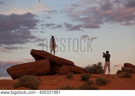 Horseshoe Bend, Arizona / Usa - October 25, 2014:  A Man Takes A Picture Of A Woman Standing On An O
