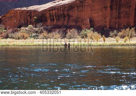 Horseshoe Bend, Arizona / Usa - October 30, 2014:  A Couple And Their Dog Wading Into The Colorado R