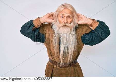 Old senior man with grey hair and long beard wearing viking traditional costume trying to hear both hands on ear gesture, curious for gossip. hearing problem, deaf