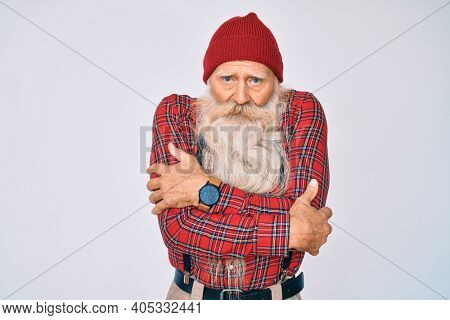 Old senior man with grey hair and long beard wearing hipster look with wool cap shaking and freezing for winter cold with sad and shock expression on face