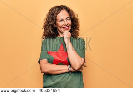 Middle age beautiful woman wearing t-shirt with red star revolutionary symbol of communism smiling looking confident at the camera with crossed arms and hand on chin. Thinking positive.