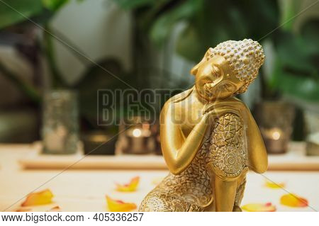 Golden Bronze Buddha Decorative Statuette With Flower Petals On The Wooden Table With Burnig Candles