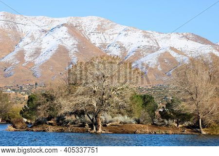 Barren Mountains Covered With Snow Surrounding A Lake Besides A Riparian Woodland Taken At The Mojav