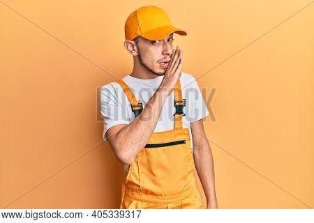Hispanic young man wearing handyman uniform hand on mouth telling secret rumor, whispering malicious talk conversation