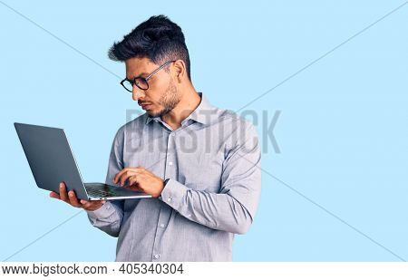 Handsome latin american young man working using computer laptop thinking attitude and sober expression looking self confident