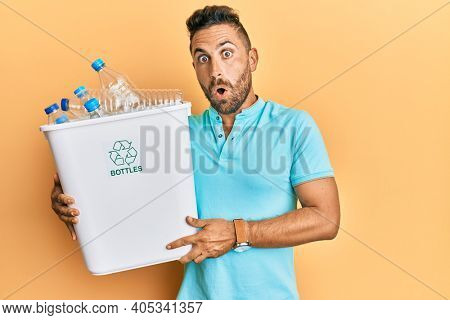 Handsome man with beard holding recycling wastebasket with plastic bottles scared and amazed with open mouth for surprise, disbelief face