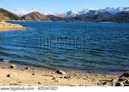 Snow Capped Mountains Surrounding A Remote Sandy Beach Cove At Silverwood Lake, Ca Taken In The Rura
