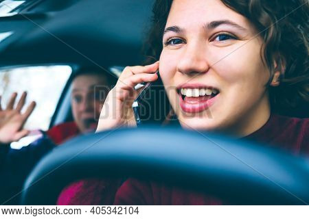 Happy Curly Haired Girl Talking On Mobile Phone While Driving Car. Man In Next Seat Is Terrified Of
