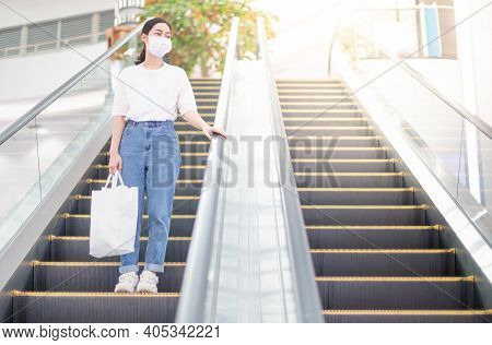 Female Hand Wearing Surgical Mask And  Touching Escalator Handrail While Using Escalator In Shopping