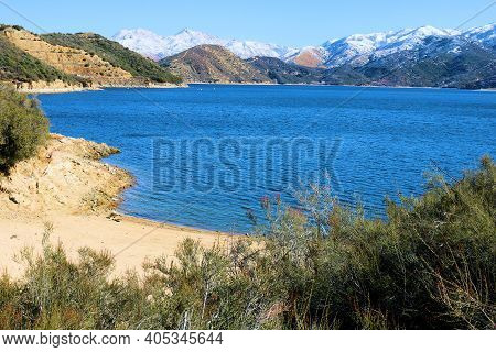 Sandy Beach Cove Surrounded By Snow Capped Mountains Taken At Silverwood Lake, Ca In The Mojave Dese