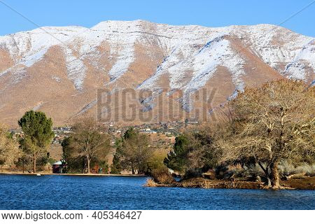 Lake Surrounded By Deciduous Trees With Snow Covered Mountains Beyond Taken At The Mojave Desert In