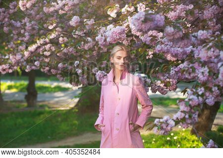 Spring Fashion, Girl In Pink Coat Enjoy Blossom Sakura In Garden. Flowers Make Women Happy. Spring B