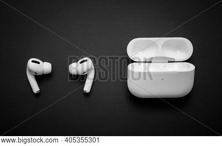 Belgrade, Serbia - January 2021. Apple AirPods Pro on black background. Wireless headphones and charging case