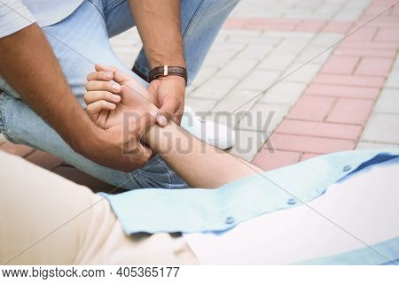 Passerby Checking Pulse Of Unconscious Young Man Outdoors, Closeup. First Aid