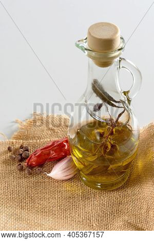 Olive Oil And A Sprig Of Olive In A Glass Jug Standing On A Burlap Sack. A Pod Of Hot Red Pepper, Ga