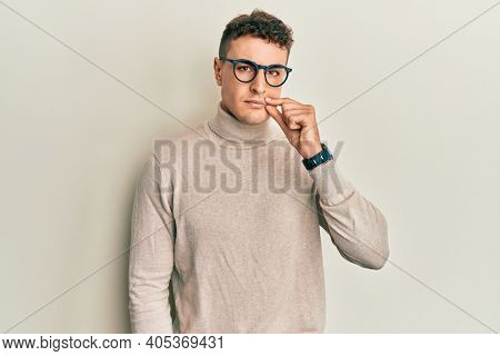 Hispanic young man wearing casual turtleneck sweater mouth and lips shut as zip with fingers. secret and silent, taboo talking