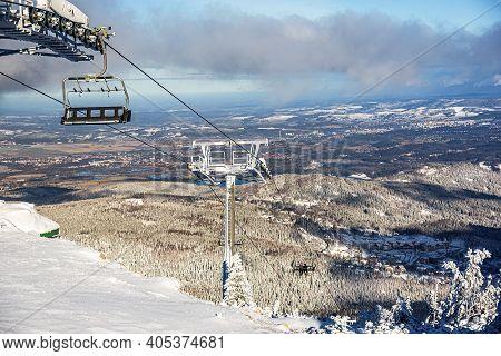 Poland, Mountain Tourist Lift , Ski Lift In The Mountains In Winter . Ski Lift Chairs On Bright Day