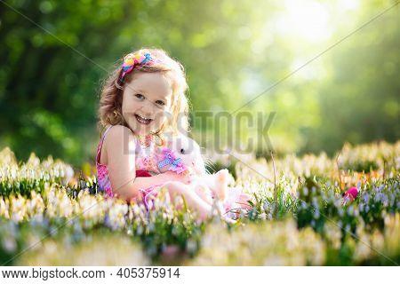Child Playing With White Rabbit. Little Girl Feeding And Petting White Bunny. Easter Celebration. Eg