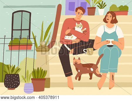 Young Couple Spending Leisure Time Together With Cats On The Front Porch Of House, Drinking Tea, Rel