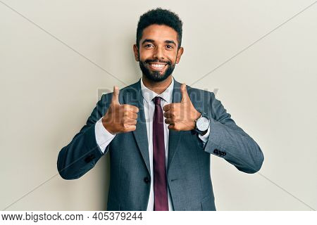 Handsome hispanic man with beard wearing business suit and tie success sign doing positive gesture with hand, thumbs up smiling and happy. cheerful expression and winner gesture.