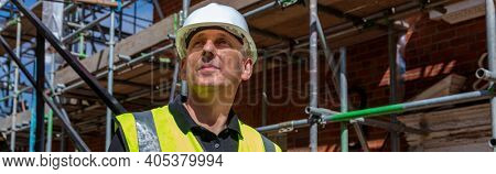 Panorama of male builder foreman, worker, surveyor, engineer or architect wearing hard hat on construction site panoramic web banner