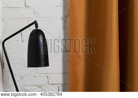 Black Reading Lamp On Background Of White Brick Wall And Gold Portiere. Interior Of A Loft Space, A
