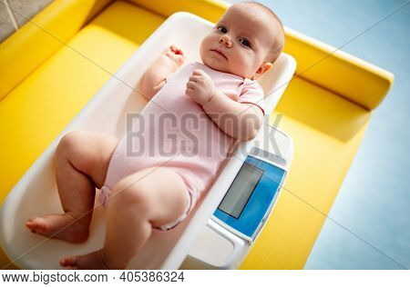 Beautiful Newborn Baby On Weighing Scale. Health, Baby Weight Concept.