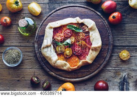 Savory Galette With Fresh Colorful Tomatoes And Basil On Wooden Table. Vegetarian Healthy Food Conce