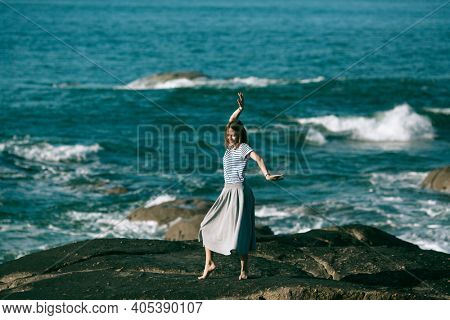 The dancer woman is engaged in choreography on the rocky Alantic coast.