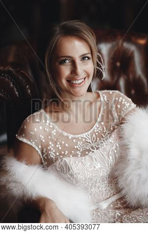 A Gorgeous Young Woman In A Luxurious White Dress And White Fur Cape Sits In A Luxurious Leather Arm