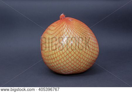 Chinese Pomelo Fruit In A Red Mesh On A Dark Background.