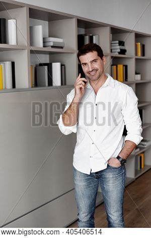 Cheerful Businessman Talking On Stationary Phone In Office Standing Behind Workplace, Looking At Cam