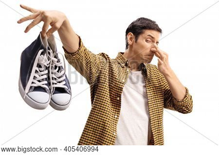 Guy holding a pair of smelly trainers isolated on white background