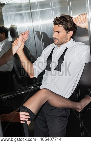 Passionate Man In White Shirt And Untied Tie Seducing Sexy Woman In Elevator.