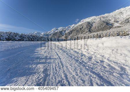 Snow Covered Walking Path Through Sunny Alpine Winter Landscape In Wildermieming, Tirol, Austria