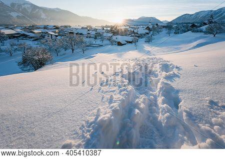 Deep Snow Track Through Winter Landscape During Sunset In Alpine Village With Sun Star Between Mount