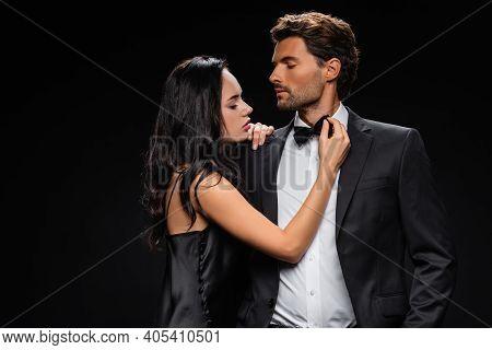 Passionate Woman In Satin Dress Seducing Confident Elegant Man Isolated On Black.