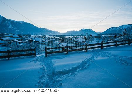 Snow Tracks In Alpine Winter Landscape During Blue Hour Dusk With View Over Small Austrian Tradition