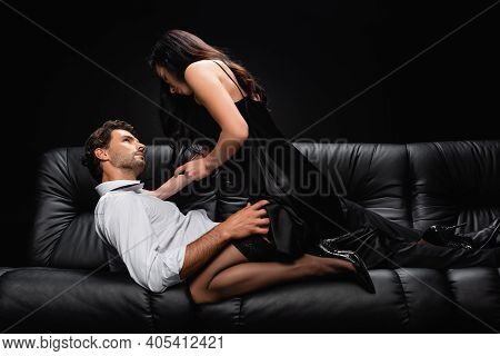 Passionate Elegant Woman Seducing Man Lying On Leather Sofa Isolated On Black.