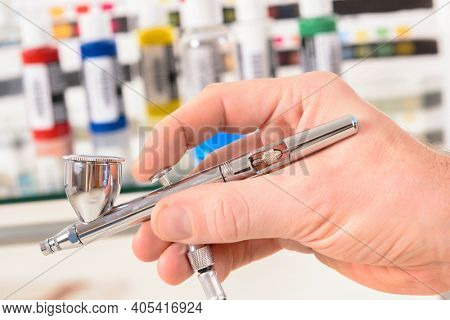 Hand holding a professional airbrush and bottles with paint