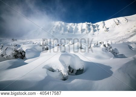 Snow wavy surface created by a wind on the frozen slope. Abstract winter backdrop. Forms of snow relief, covered ground texture. Location place Carpathian mountains, Ukraine, Europe. Beauty of world.