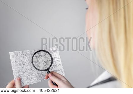 A Neurologist With A Magnifying Glass Examines An Encephalogram Of A Patient's Brain. Schedule Of El