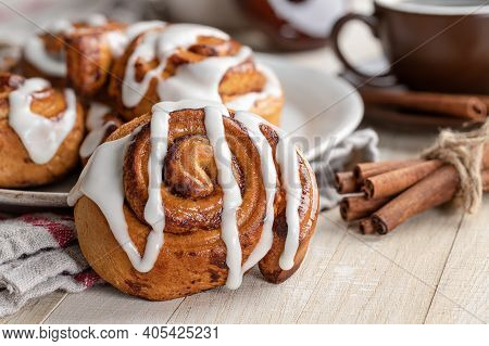 Closeup Of A Baked Cinnamon Roll With White Icing On A Wooden Table