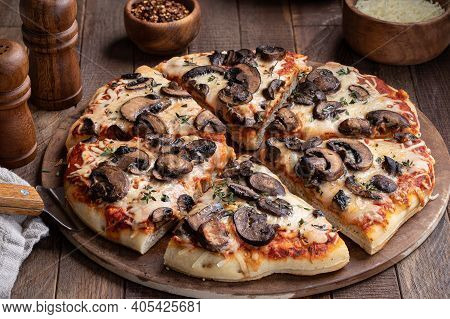 Slices Of Mushroom And Cheese Pizza With Fresh Thyme On A Baking Stone