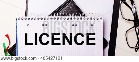 The Word Licence Is Written In Red In A White Notebook Next To Black-framed Glasses.