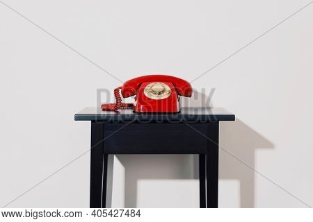a red landline rotary dial telephone on a black wooden table, indoors, in front of a white wall