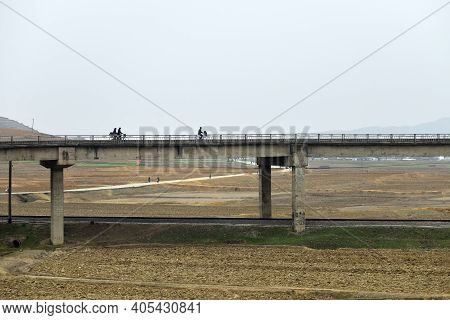 North Korea - April 30, 2019: Local People Pass The Modern Overhead Road Over Cultivated Agricultura
