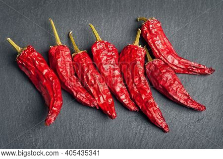 Red Pepper. Dry Peppers Are Spread Out On A Black Slate Stone. Hot Chili Peppers. Spices For Cooking