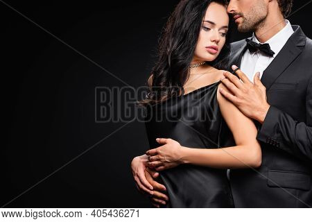 Young Man Seducing Sensual Brunette Woman In Satin Dress Isolated On Black.
